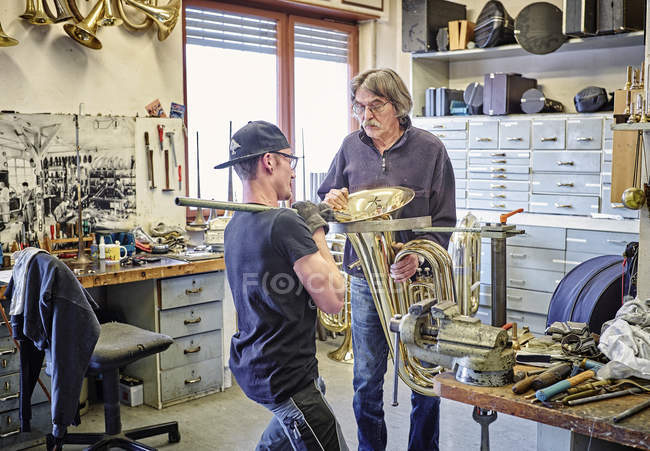 Два производителя инструментов ремонтируют медный инструмент в мастерской — стоковое фото