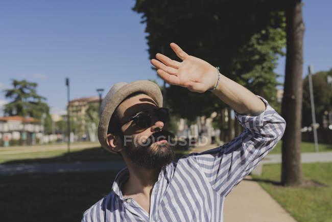 Человек в шляпе, с зажмуренными глазами на улице — стоковое фото