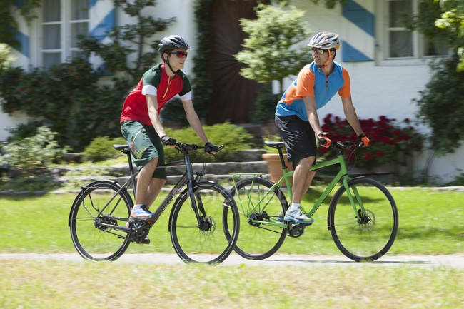 Mid adult man and teenage boy on a bicycle tour with trekking bikes — Stock Photo