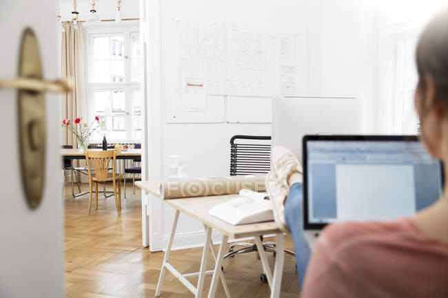 Woman using laptop in modern office with feet up — Stock Photo