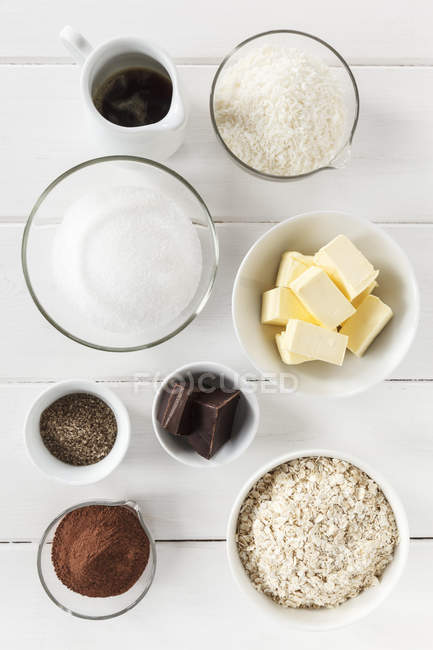 Bowls of ingredients for coco chocolate truffles on white wooden table, studio shot — Stock Photo
