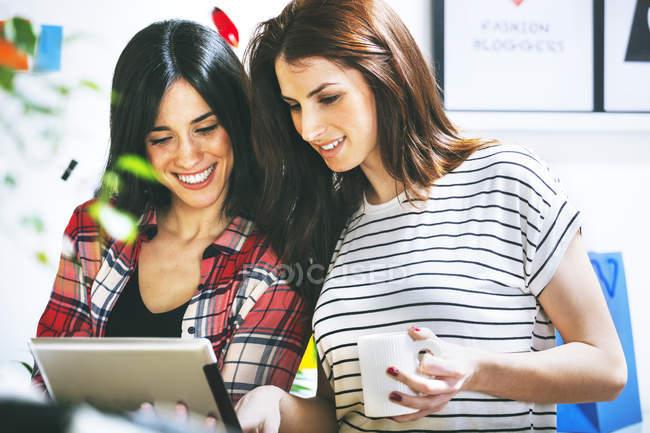 Due fashion blogger donne che usano il tablet digitale in ufficio — Foto stock