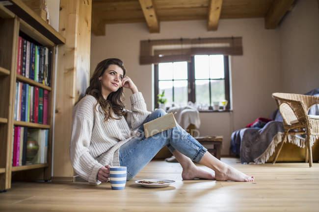 Jeune femme à la maison lire un livre — Photo de stock