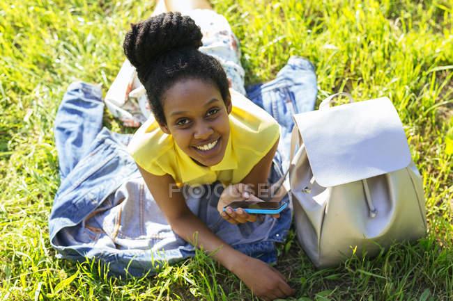 Portrait de jeune femme avec smartphone et sac à dos relaxant sur une prairie — Photo de stock