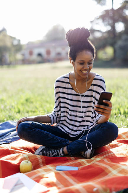 Portrait of smiling woman sitting on blanket hearing music with earphones — Stock Photo