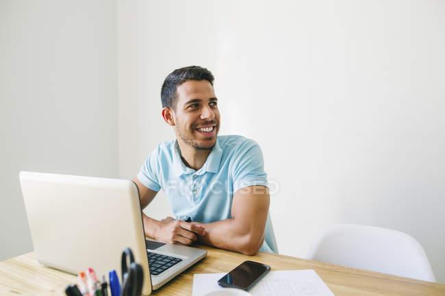 Jovem sorridente trabalhando no escritório com laptop — Fotografia de Stock