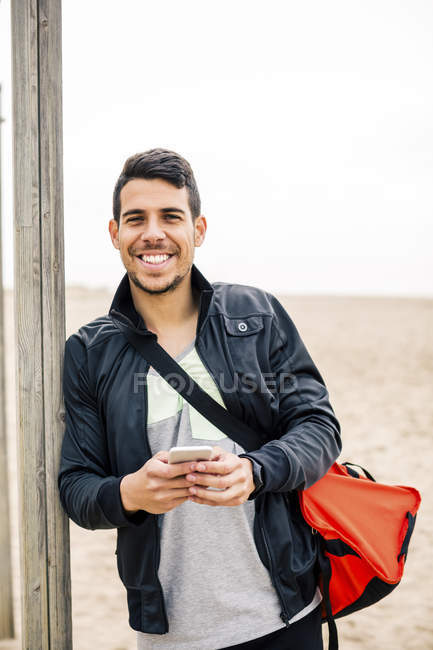 Smiling young man leaning against wooden stake on beach — Stock Photo
