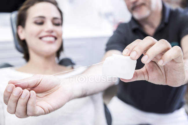 Woman getting dental floss explained — Stock Photo