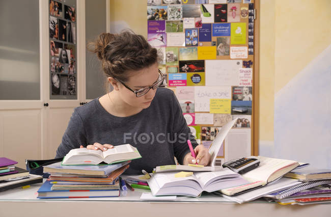 Élève faisant ses devoirs au bureau avec une pile de livres — Photo de stock
