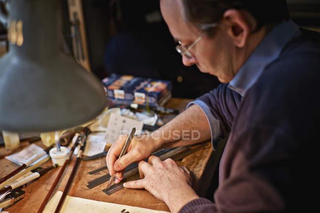 Violin maker cutting veneer strips in workshop — Stock Photo