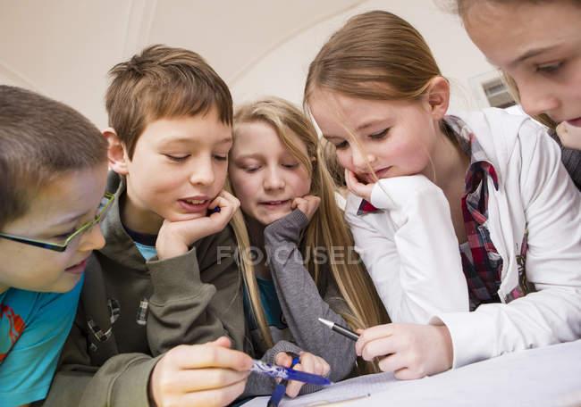 Groupe d'enfants apprenant ensemble en classe — Photo de stock