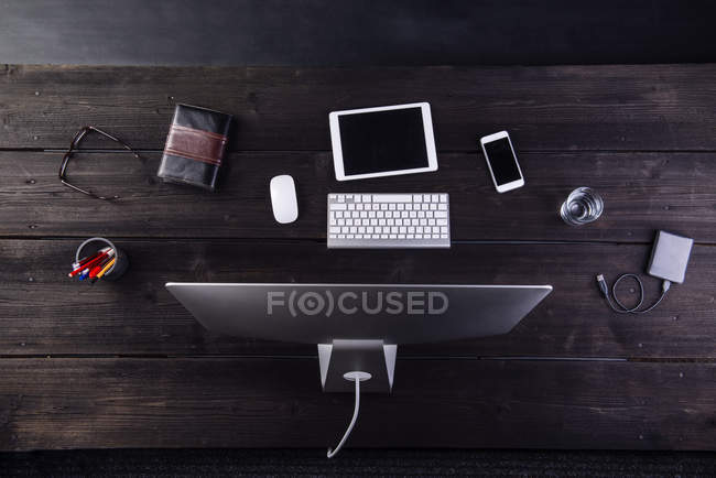 Desk with computer and various digital gadgets — Stock Photo