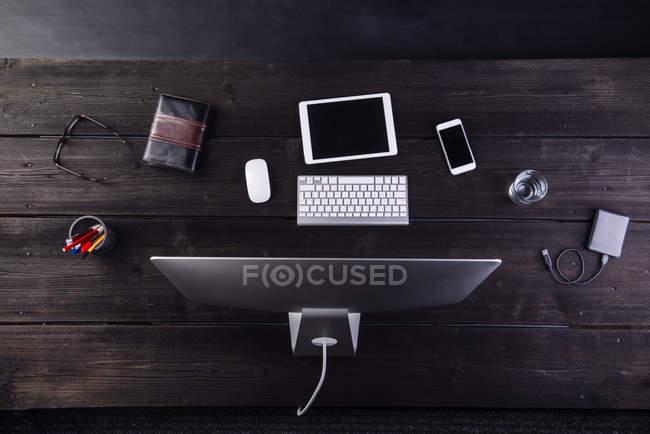 Scrivania con computer e vari gadget digitali — Foto stock