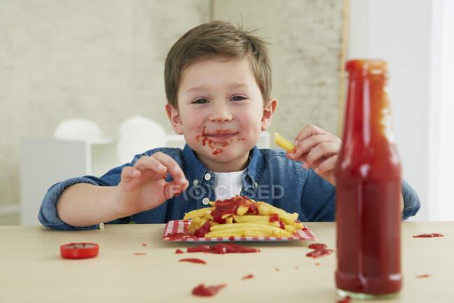 Мальчик ест картошку фри с кетчупом — стоковое фото
