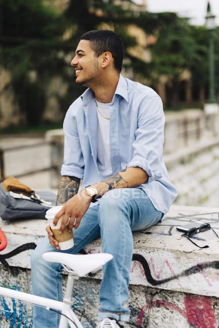 Smiling young man sitting on graffiti wall — Stock Photo