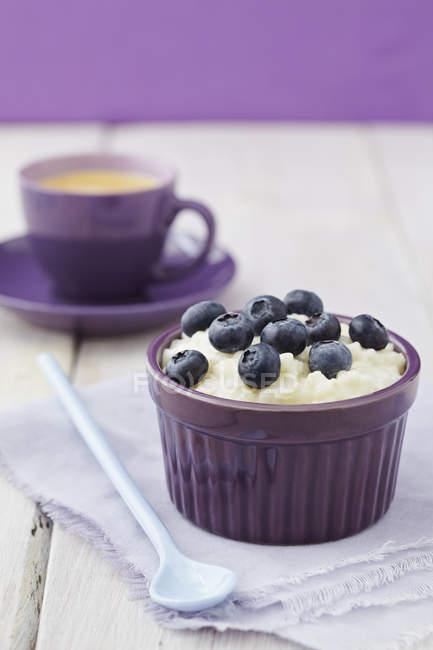 Миску молока рисовый пудинг с черникой и кофе в фоновом режиме — стоковое фото