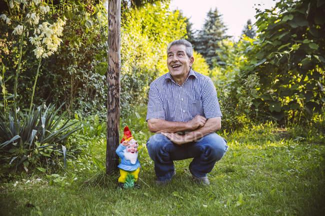 Senior homme accroupi par gardengnome au jardin — Photo de stock