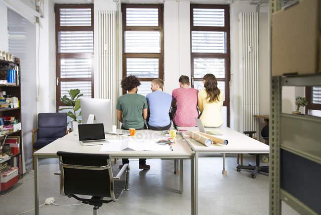 Команда креативных профессионалов, сидящих за столом в офисе — стоковое фото