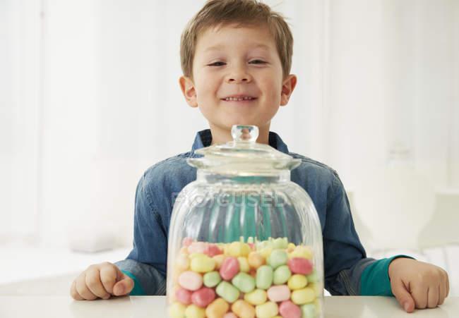 Garçon avec bonbons pot souriant à la caméra — Photo de stock