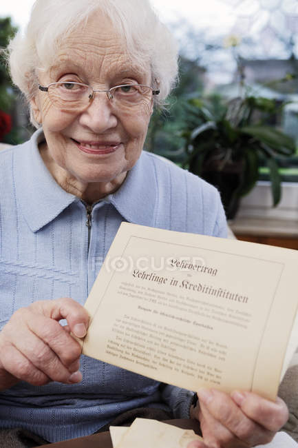 Senior woman showing her old training contract — Stock Photo