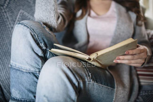 Junge Frau liest zu Hause ein Buch — Stockfoto