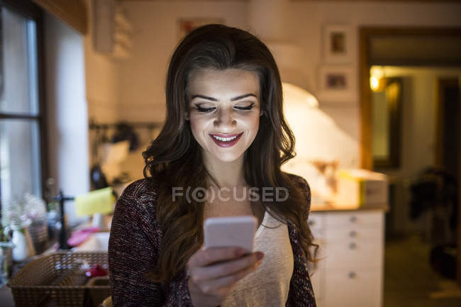Junge Frau zu Hause mittels smartphone — Stockfoto