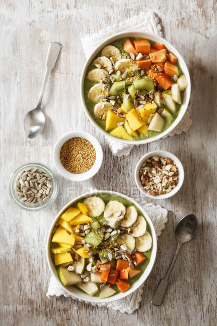 Smoothie bowls with mango, papaya, kiwi, banana, pear, lineseeds, sunflower-seeds and nuts — Stock Photo