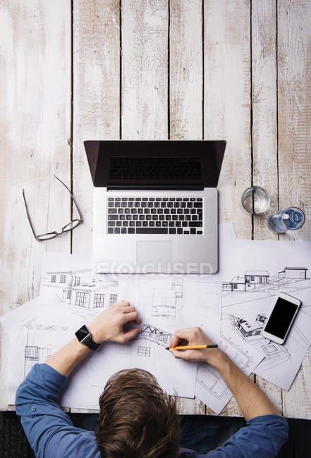 Architetto che lavora alla scrivania con computer portatile, facendo schizzi — Foto stock