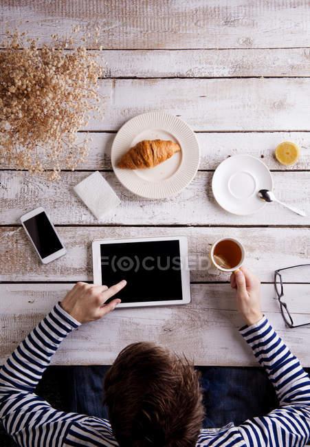 Mann am Tisch mit Croissant und Tee, arbeitet mit digital-Tablette — Stockfoto