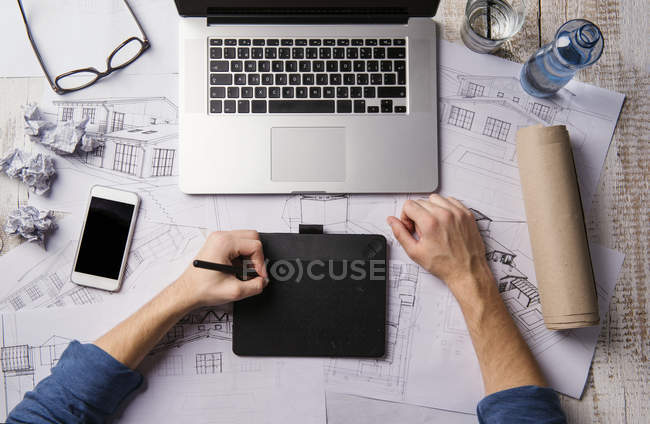 Architect working at desk with laptop, making sketches — Stock Photo