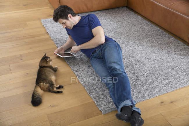 Uomo con tablet digitale sdraiato sul pavimento, gatto che lo osserva — Foto stock