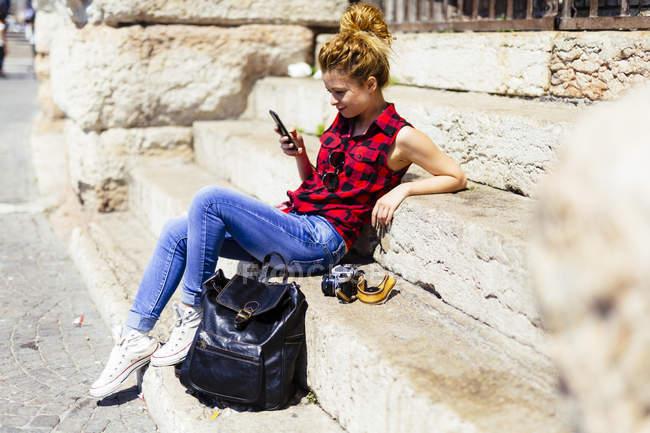 Italia, Verona, donna seduta sulle scale che guarda il cellulare — Foto stock