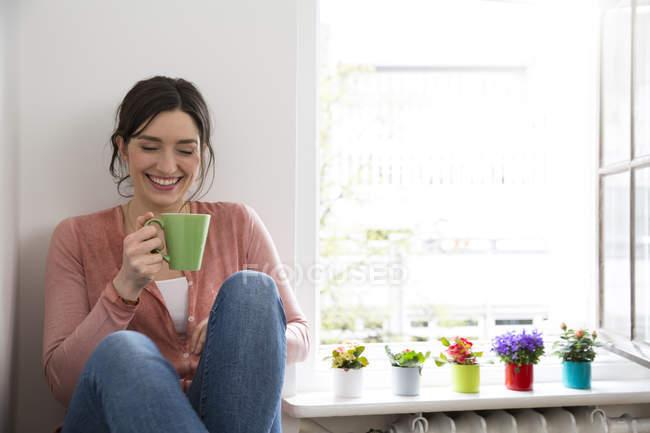 Donna felice con tazza di caffè seduta alla finestra — Foto stock