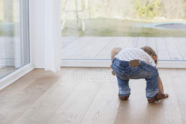 Малыш поднимается с пола, вид сзади — стоковое фото