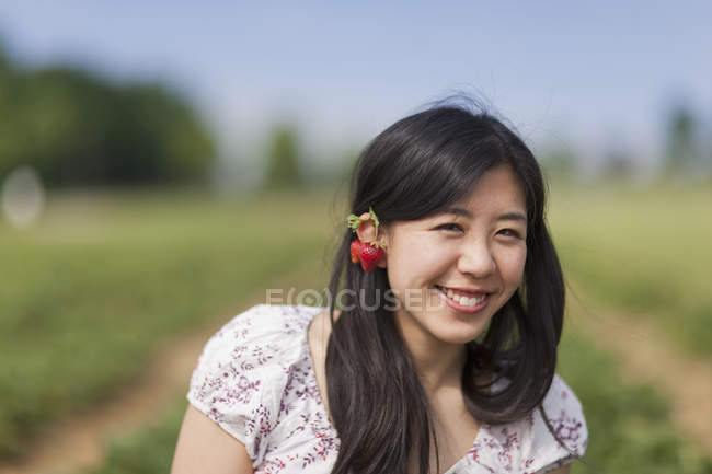 Young Japanese woman with strawberry earrings portrait — Stock Photo
