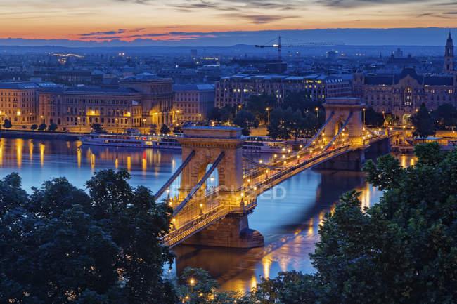 Hungria, Budapeste, Vista iluminada para a Peste com ponte Chain e rio Danúbio à noite — Fotografia de Stock
