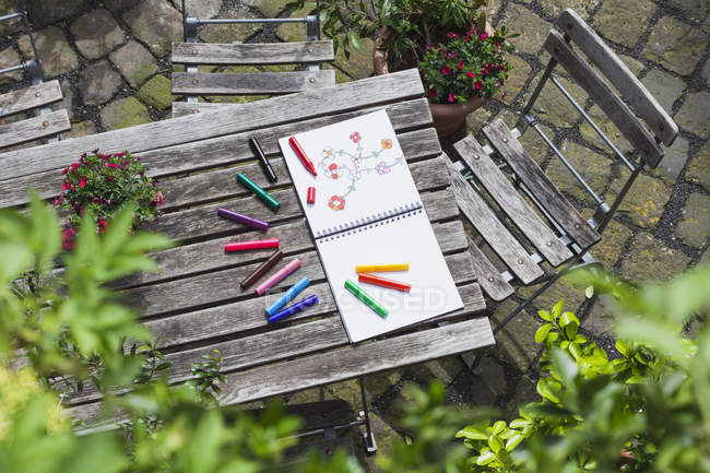 Drawing, sketch book with drawing and coloring pencils on wooden garden table — Stock Photo