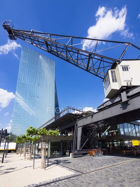 Німеччина, Гессен, Франкфурт, нові будівлі з Європейського Центрального банку з Старого порту крана на передньому плані — стокове фото