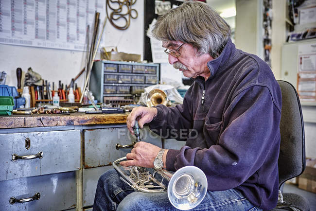 Instrument maker repairing trumpet in workshop — Stock Photo