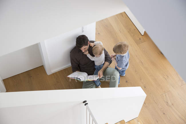 Father and sons sitting on floor, reading book — Stock Photo