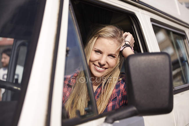 Smiling young woman in minivan — Stock Photo