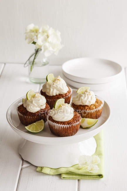 Four lime cupcakes with cream cheese topping on cake stand — Stock Photo