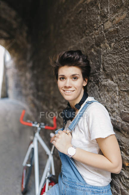 Portrait of smiling young woman with bicycle at stone wall — Stock Photo