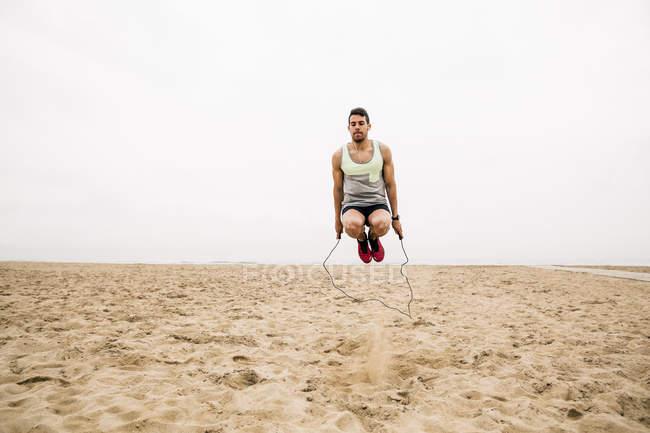 Jeune homme corde à sauter sur la plage de sable fin — Photo de stock