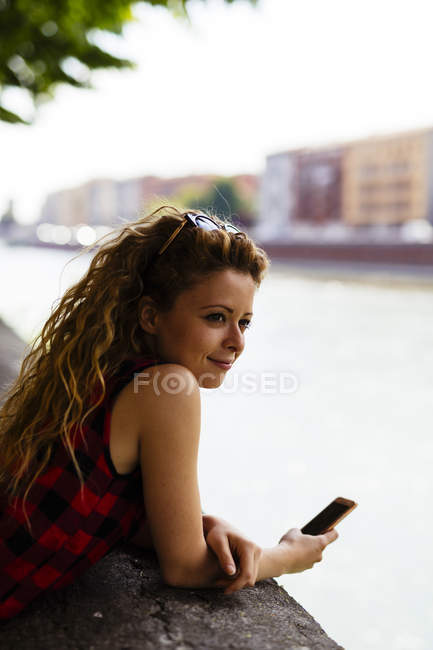 Italy, Verona, woman at the riverside holding cell phone — Stock Photo