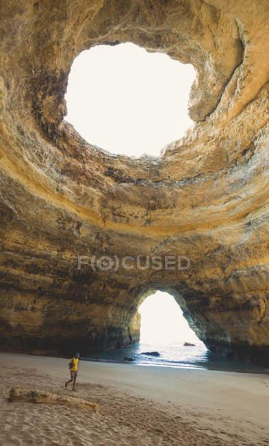 Чоловік, що стоїть в рок-печера Praia de Benagil — стокове фото