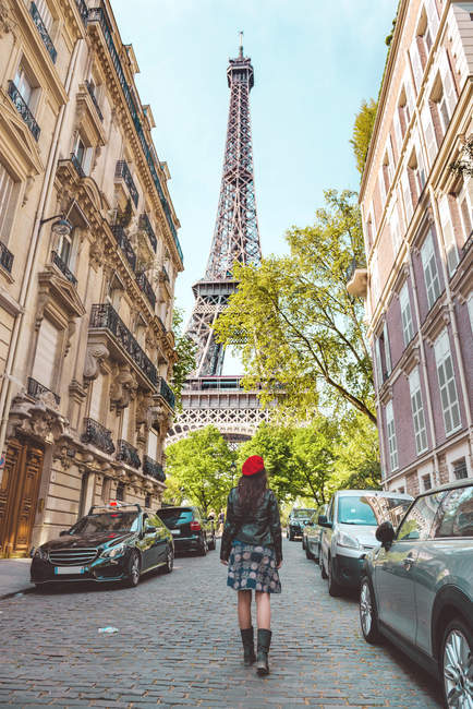 France, Paris, Eiffel Tower among the buildings, nearby street and woman wearing a red beret walking on the street — Stock Photo