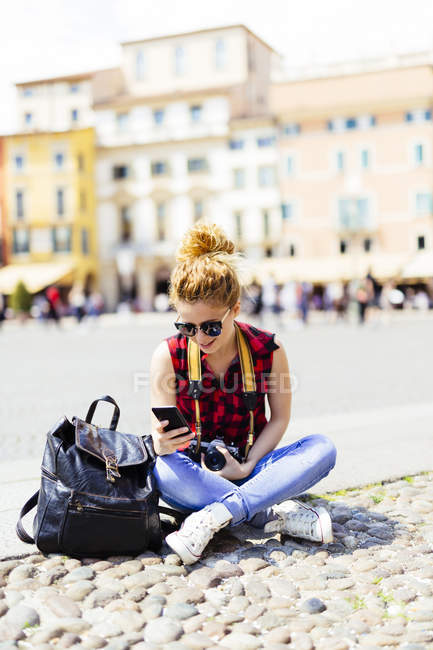 Italy, Verona, woman on town square looking at cell phone — Stock Photo