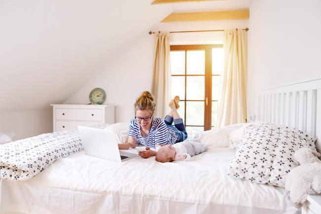 Madre con bambino, telefono cellulare e laptop sul letto — Foto stock