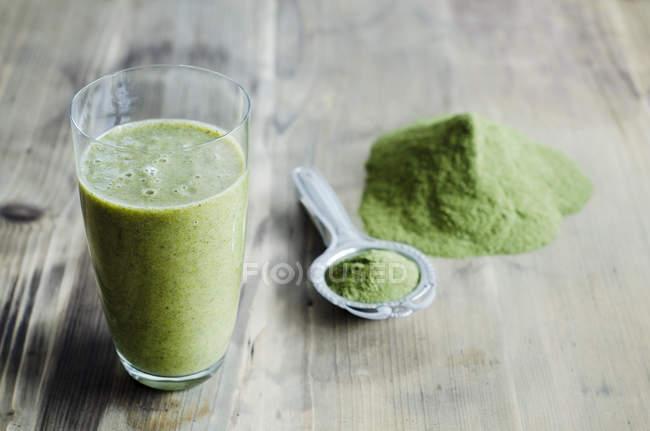 Moringa powder on spoon with glass of moringa smoothie on wooden surface — Stock Photo